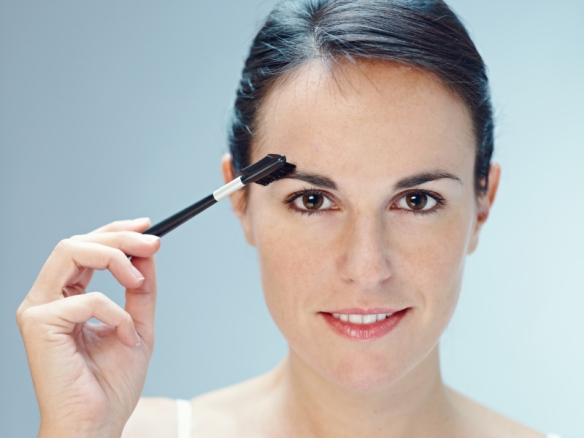 close up of woman brushing eyebrows with makeup brush. Copy space